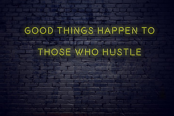 Positive inspiring quote on neon sign against brick wall good things happen to those who hustle