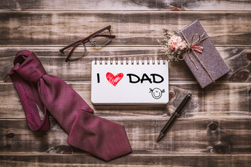 Father's day background concept. Flat lay image of gift box, necktie, glasses and notebook with text I love dad on wooden background. Flat lay Top view.