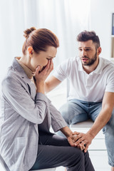 man consoling crying woman during therapy meeting