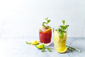 Home made Apple-Lemon and Raspberry-Lemon Lemonade with mint leaves and ice. Summer fruit drinks. Copy space