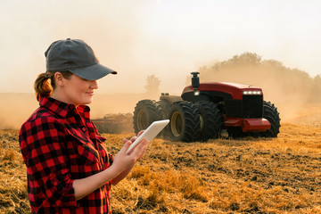 Wall Mural - Woman  farmer with digital tablet controls an autonomous tractor on a smart farm