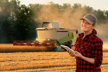 Etiqueta Engomada - Woman farmer uses a digital tablet control autonomous harvester. Smart farming concept