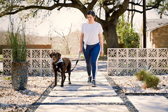 Woman with dog walking on footpath