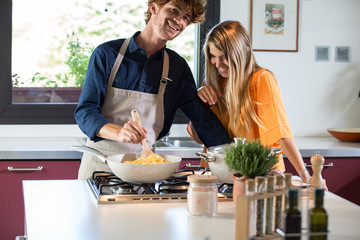 Smiling couple preparing food in kitchen at home