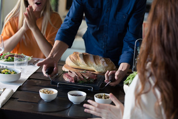 Mid section of man serving food on table