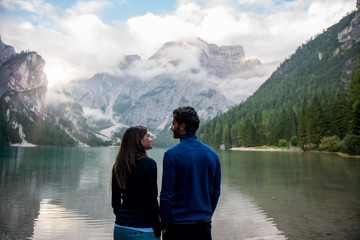 Couple standing near lake against mountain