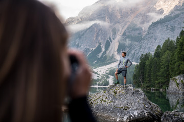 Woman taking picture of man outdoors
