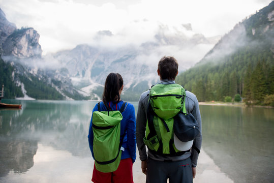 Rear view of couple standing near lake against mountain