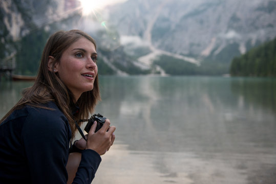 Smiling brunette woman holding camera outdoors