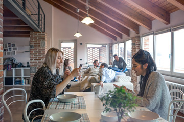 Smiling women using smartphone while sitting at dining table in home