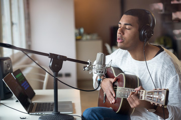 Man singing with guitar while sitting in studio