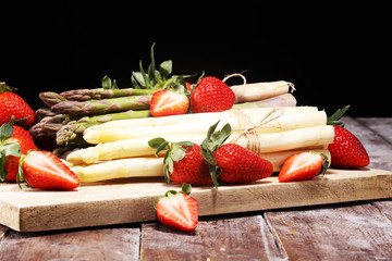 White and green asparagus with strawberries on wood