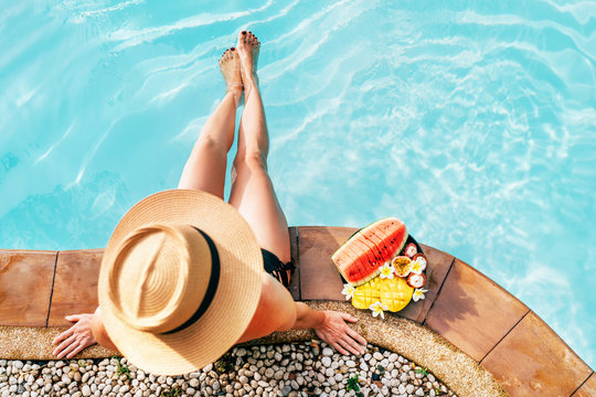 Woman in straw hat sitting on swimming pool side  with plate of tropical fruits- camera top view