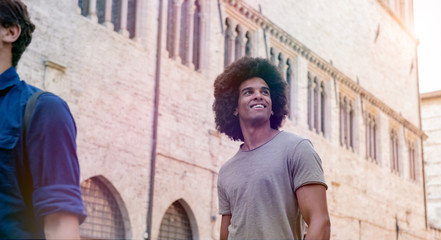 Smiling afro young man walking outdoors