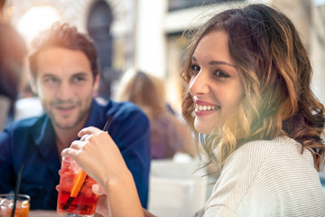 Smiling young couple sitting at outdoor cafe