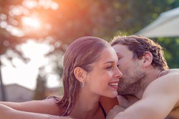 Man kissing his girlfriend at poolside