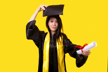 graduate with a diploma in her hand, grimaces and rejoices in the successful graduation day, image on a yellow background