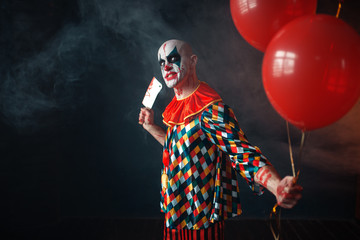 Bloody clown with meat cleaver holds air balloon Wall mural