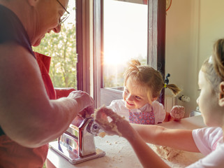 Grandmother and granddaughter making pasta in kitchen