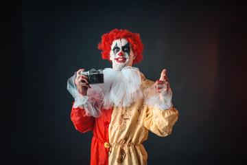 Scary bloody clown with crazy eyes makes picture