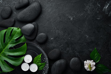 Zen stones and leaves with water drops. Spa background with spa accessories on a dark background....