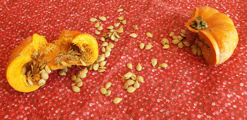 Broken pumpkin in half with scattered seeds on red material. Preparation of pumpkin seeds for drying.