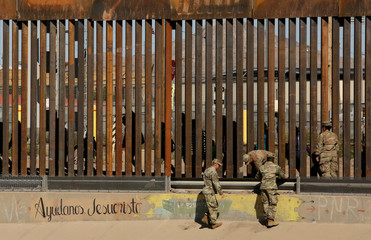 U.S. soldiers walk next to the border fence between Mexico and the United States, as migrants are seen walking behind the fence, after crossing illegally into the U.S. to turn themselves in, in El Paso, Texas, U.S., in this picture taken from Ciudad Juarez