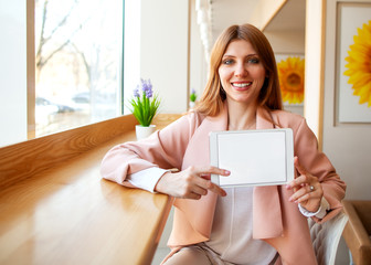 girl freelancer holding a tablet in the office