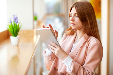 girl freelancer holding a tablet in the cafe