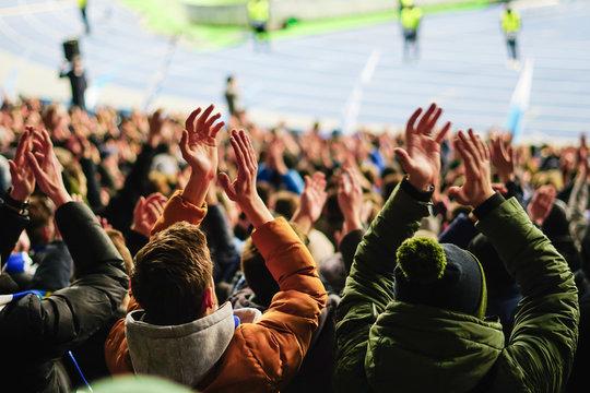 Football fans raising hands, chanting, supporting national team at stadium