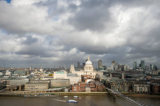 Scenic overcast view of the city skyline with a patch of sun lighting St Paul's Cathedral above the River Thames in London, England
