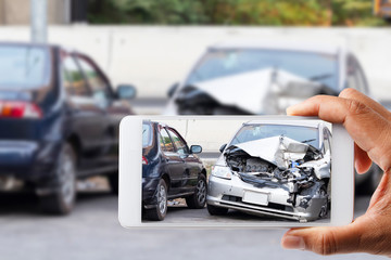 Car insurance agents take pictures of accident-damaged with smartphone for insurance claim