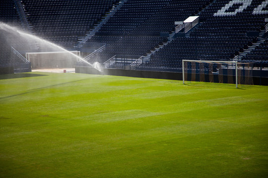 Water jets sprinkling a football Stadium.