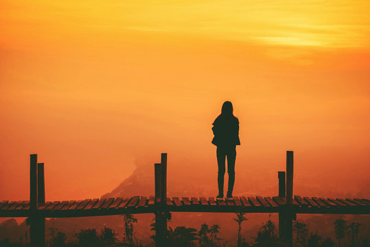 Silhouette woman standing on wooden bridge on hill mountain and sunset yellow sky background