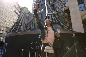 "A fan takes a picture in front of a large replica of the iron throne outside the premiere of the final season of ""Game of Thrones"" at Radio City Music Hall in New York"