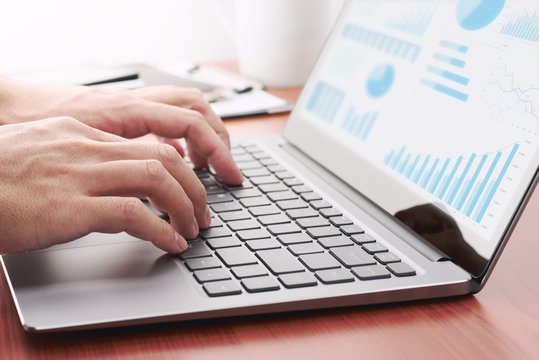 Business analytics concept. Businessman preparing reports.Laptop and many graphs.