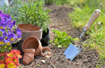 trowel planting in the dirt next to flowerpots in a garden