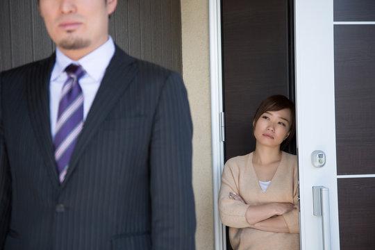 玄関で夫を送り出す妻