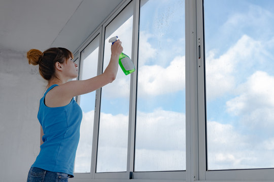 The girl sprays liquid for washing windows on dirty glass. A woman in a blue t-shirt and denim shorts washes a window.