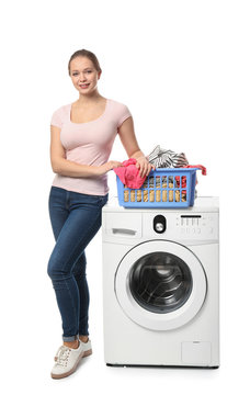 Young woman with washing machine on white background