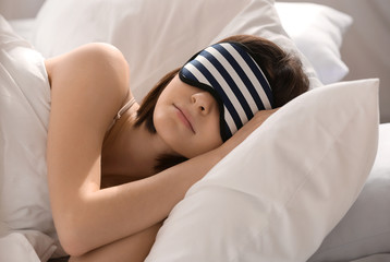 Young woman with sleep mask in bed