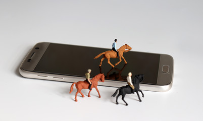 Three miniature horses with riders and a smartphone.