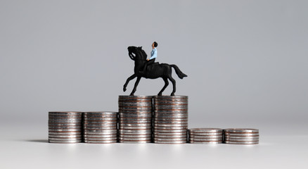 A miniature man riding horses on piles of coins. Three pile of coins in the shape of a podium.