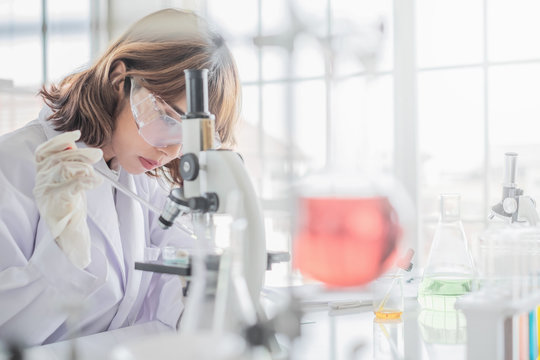 A young Asian woman scientist working in laboratory with test tube microscope and solutions.