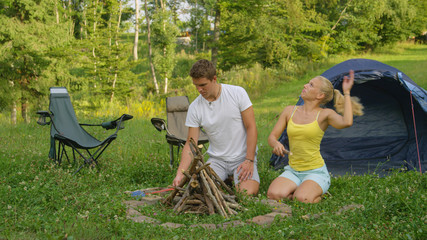 Beautiful girl gets swarmed by bugs while her boyfriend prepares a campfire.