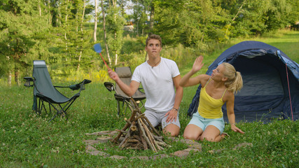 Man starts flailing a fly swatter as the couple gets attacked by irritating bugs