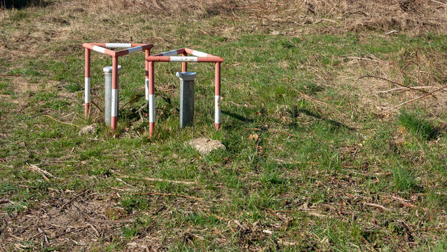 Groundwater measuring points with steel protection tube, end cap with hex locking and red and white concreted protection triangle