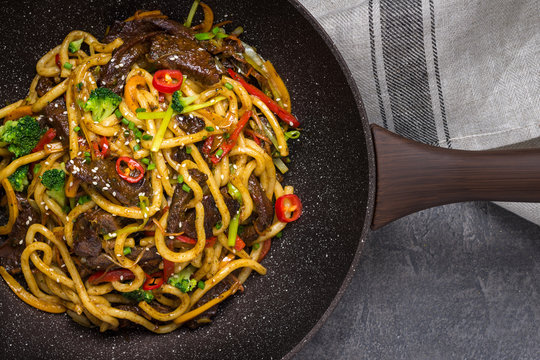 Udon Stir-Fry Noodles with Beef and Vegetables in Wok Pan on Dark Background