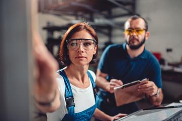 Female worker operate machine in factory