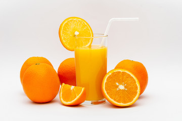 glass of orange juice and oranges on a white background